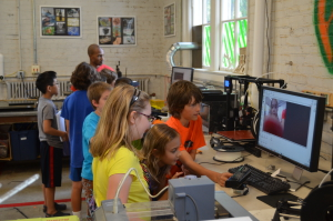 Participants in Minecraft camp learning how to do 3D scans, to import themselves into the game as statues.